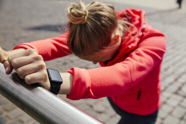 Young sporty woman with smart watch stretching - MFF001863