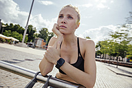 Young sporty woman with smart watch leaning on railing - MFF001865
