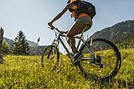 Austria, Tyrol, Tannheim Valley, young woman on mountain bike in alpine landscape - UUF004937