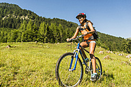 Austria, Tyrol, Tannheim Valley, happy young woman on mountain bike in alpine landscape - UUF004938