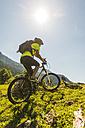 Austria, Tyrol, Tannheim Valley, young man on mountain bike in alpine landscape - UUF004944