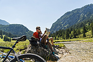 Austria, Tyrol, Tannheim Valley, young couple with mountain bikes and map sitting at brook - UUF004959