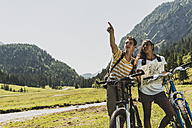 Austria, Tyrol, Tannheim Valley, young couple with mountain bikes and map in alpine landscape - UU004962