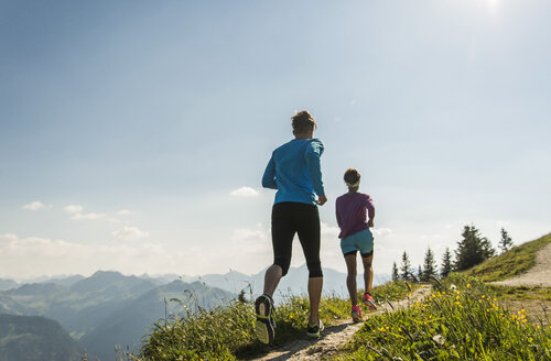 Austria, Tyrol, Tannheim Valley, young couple jogging in mountains - UUF004970