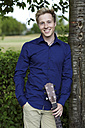 Smiling young man with guitar at tree - GDF000794