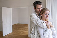 Young couple in empty apartment looking away in thought - CHAF000562