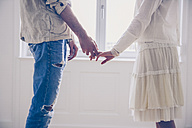 Mid-section of couple standing hand in hand at the window - CHAF000565