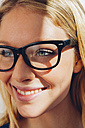 Close-up of smiling young woman wearing glasses - CHAF000573