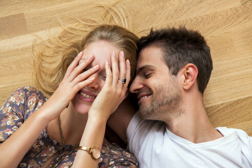 Top view of happy young couple lying on floor - CHAF000575