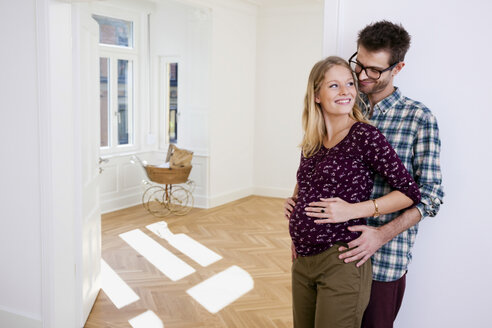 Young man embracing pregnant woman in new home with pram in background - CHAF000585