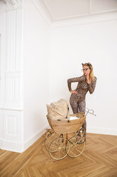 Young woman wearing animal print bodysuit looking at pram - CHAF000601