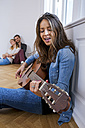 Young woman sitting on floor playing guitar with couple in background - CHAF000604