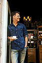 Mature man leaning in door of cafe, holding cup of coffee - CHAF000771
