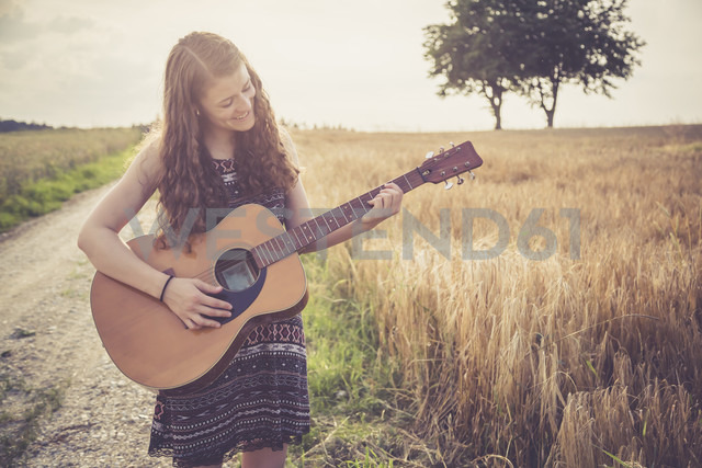 Young woman playing guitar, field in the evening - SARF002052