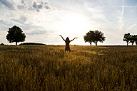 Young woman standing in barley field with raised arms in the evening - SARF002054
