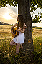 Young woman with guitar leaning on tree trunk, barley field in the evening - SARF002043