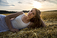 Young woman lying on field in the evening - SARF002045
