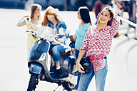 Portrait of teenage girl holding motorcycle helmet while her friends with scooter waiting at background - CHAF000785