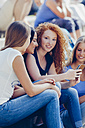 Portrait of teenage girl with a mobile phone sitting amongst her female friends - CHAF000793
