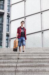 Germany, Berlin, teenage boy with  suitcase walking downstairs - MMFF000859