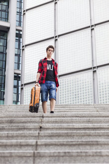 Germany, Berlin, teenage boy with  suitcase walking downstairs - MMFF000859