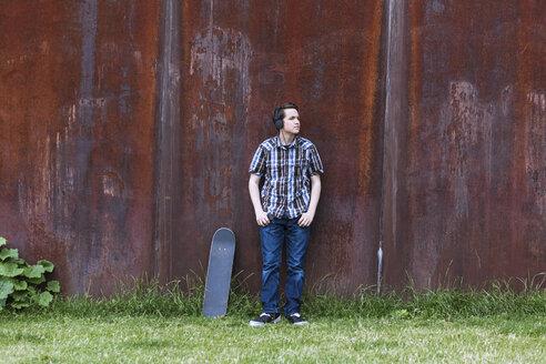 Teenage boy with skateboard leaning on corten wall hearing music - MMFF000861