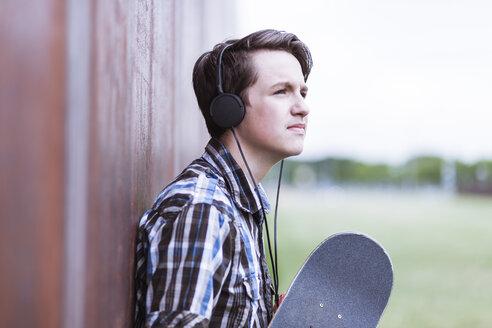 Teenage boy with skateboard leaning on corten wall hearing music - MMFF000863