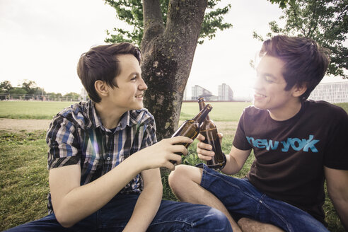 Germany, Berlin, two teenage boys sitting under a tree toasting with beer bottles - MMFF000879