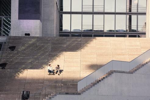 Germany, Berlin, two teenage boys sitting on stairs - MMFF000872