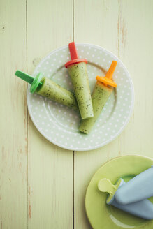 Three kiwi banana popsicles on a plate - IPF000221