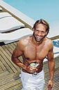 Smiling man with cocktail at pool edge - CHAF000612