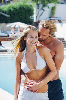 Happy couple embracing by swimming pool - CHAF000628