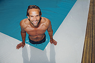 Portrait of smiling man getting out of swimming pool - CHAF000636
