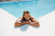 Portrait of smiling man in swimming pool leaning on pool edge - CHAF000639