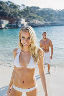 Spain, Majorca, smiling woman in bikini on the beach with man in background - CHAF000654
