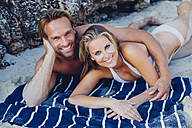Smiling couple lying on the beach - CHAF000671