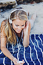 Smiling woman relaxing and listening music on the beach - CHAF000965
