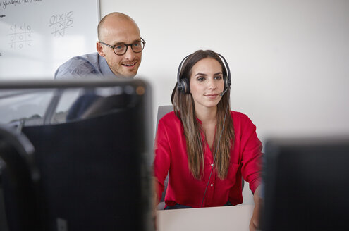 Man and woman with headset in office - RHF000909