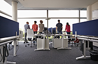 Colleagues in open-plan office standing at the window - RHF000915