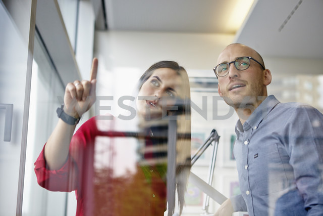 Man and woman in office discussing behind glass pane - RHF000926