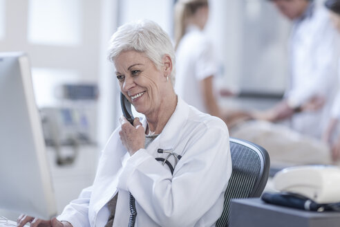Smiling senior woman in lab coat on the phone - ZEF005982