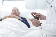 Close-up of doctor using a digital tablet next to patient - ZEF005989