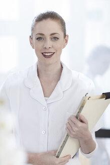 Portrait of smiling nurse holding patient file - ZEF006036