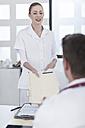 Nurse bringing patient files to doctor - ZEF006040