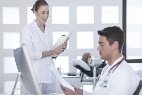 Nurse bringing patient files to doctor - ZEF006043
