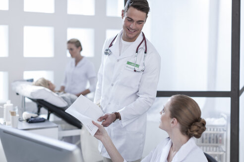 Smiling doctor handing over document to nurse - ZEF006044