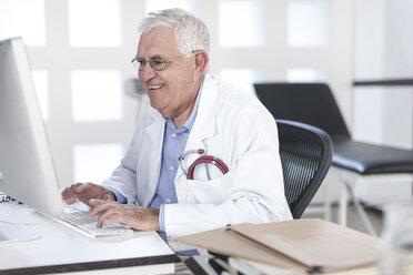 Smiling senior doctor sitting at desk working on computer - ZEF005996