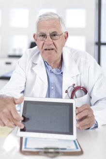 Serious senior doctor at desk showing digital tablet - ZEF005998