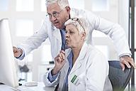 Two doctors talking at desk - ZEF006059
