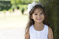 Portrait of smiling little girl leaning on a tree - GDF000811